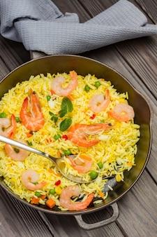 Garnalen met rijst in koekenpan. grijs servet. bovenaanzicht.