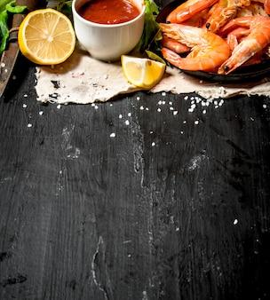 Garnalen met tomatensaus op de oude stof. op het zwarte bord.