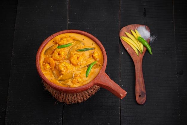 Garnalenmangocurrykerala traditioneel gerecht gemaakt van rauwe mango en gerangschikt in aardewerk