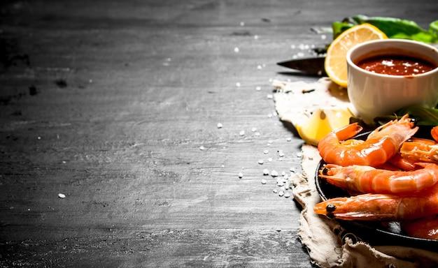 Garnalensaus, olijfolie en zout. op het zwarte bord.