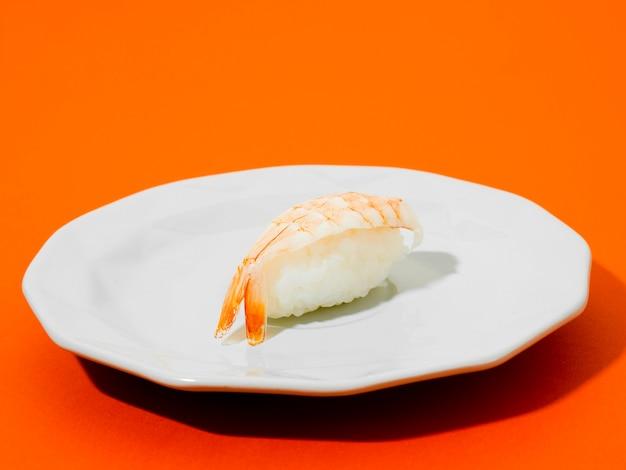 Garnalensushi op een witte plaat op oranje achtergrond