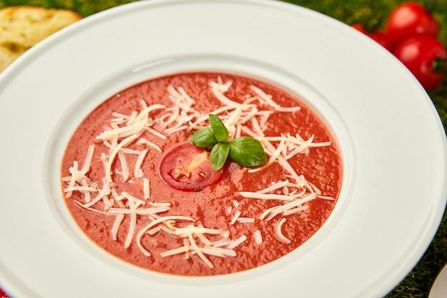 Gaspacho tomatensoep met basilicum in een kom op groen gras