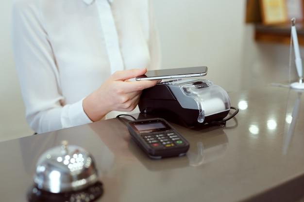 Gast bij de receptie van het hotel betaalt met check tijdens het inchecken