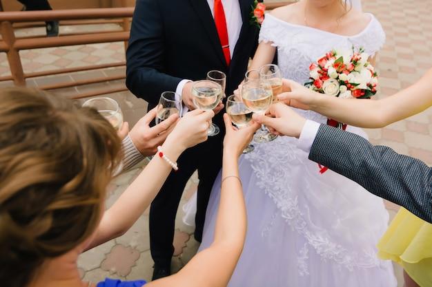 Gasten bij de bruiloft gerinkelglazen champagne en feliciteren