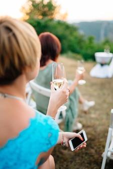 Gasten bij de huwelijksceremonie zitten en houden glazen met champagne in hun handen, terug
