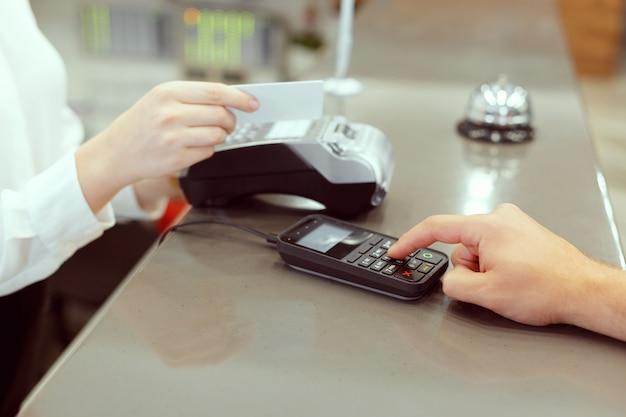 Gasten bij de receptie van het hotel betalen met cheque tijdens het inchecken