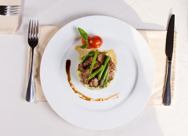 Gastronomisch gegarneerd saucy vlezig hoofdgerecht op witte ronde plaat, dineren op witte tafel met gebruiksvoorwerpen aan beide zijden van de plaat.