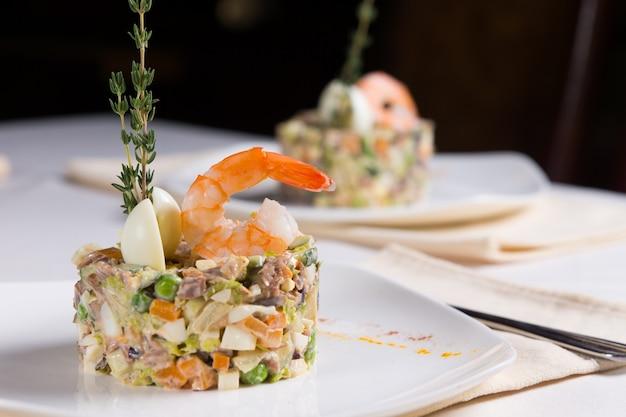Gastronomisch heerlijk hoofdgerecht recept. combinatie van zeevruchten en groenten op witte plaat. geserveerd op de tafel in het restaurant.