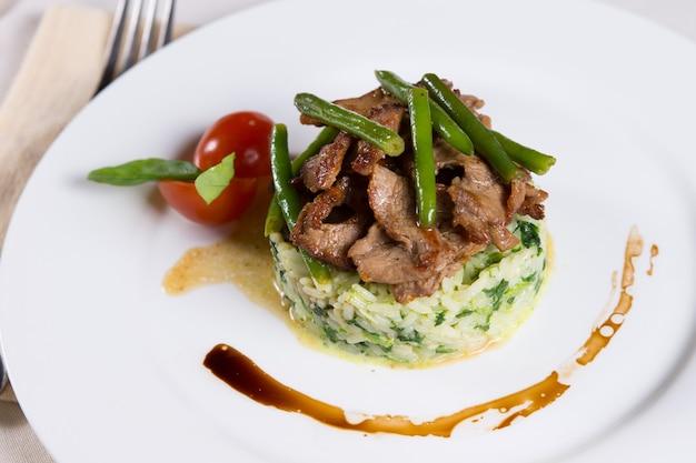 Gastronomisch lekker hoofdgerecht met goed gekookt vlees en groenten boven gearomatiseerde rijst op witte plaat.