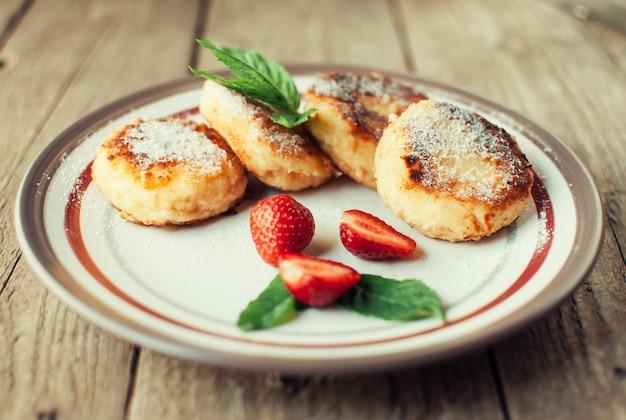 Gastronomisch ontbijt. cottage cheese pannenkoeken, cheesecakes, cottage cheese pannenkoeken met aardbeien, munt en poedersuiker in een witte plaat.