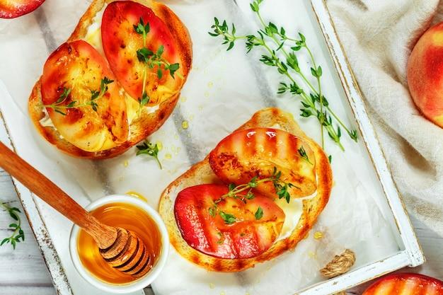 Gastronomisch zomerontbijt - broodjes (broodtoast, bruschetta) met gegrilde perziken, roomkaas