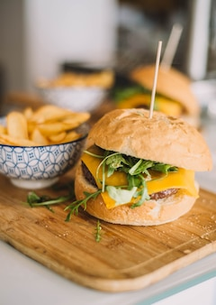 Gastronomische cheeseburger geserveerd met zelfgebakken brood en begeleid door frieten