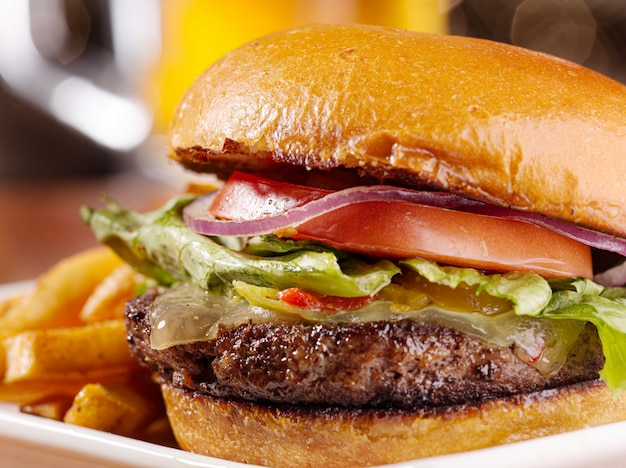Gastronomische cheeseburger met mok bier op achtergrond