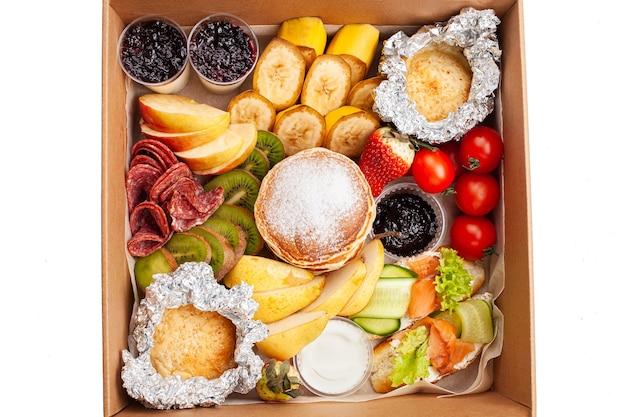 Gastronomische doos, eten. catering. een set pannenkoeken, broodjes, fruit en ontbijtproducten