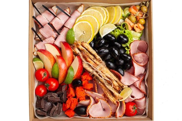 Gastronomische doos, eten. catering. een set van vlees, worst, fruit en groenten.