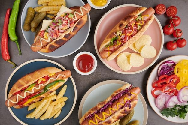 Gastronomische gegrilde runderhotdog met kanten en frietjes. heerlijke en simpele hotdogs met mosterd, paprika, ui en nacho's. hotdogs volgeladen met diverse toppings op een sup board.