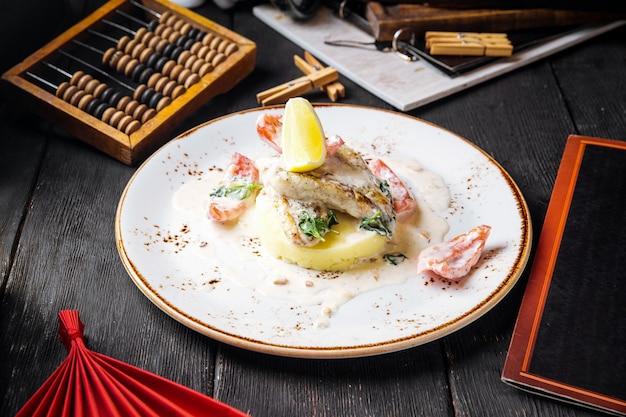 Gastronomische gekookte witte visfilet op aardappelpuree op de zwarte lijst