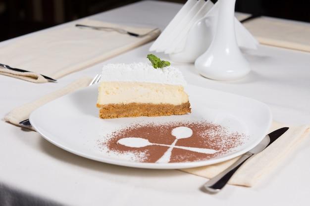 Gastronomische heerlijke drielaagse cake met lepel omtrek met cacaopoeder op witte plaat. dineer aan de witte tafel in het restaurant.