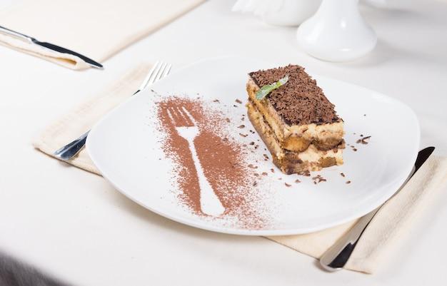 Gastronomische plak van smakelijke chocoladetaart op witte plaat met vorkomtrek met cacaopoeder aan de zijkant. geserveerd op witte eettafel.