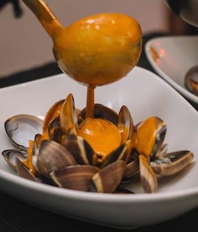 Gastronomische portie mosselen in hun sap met rode ui in een elegant restaurant
