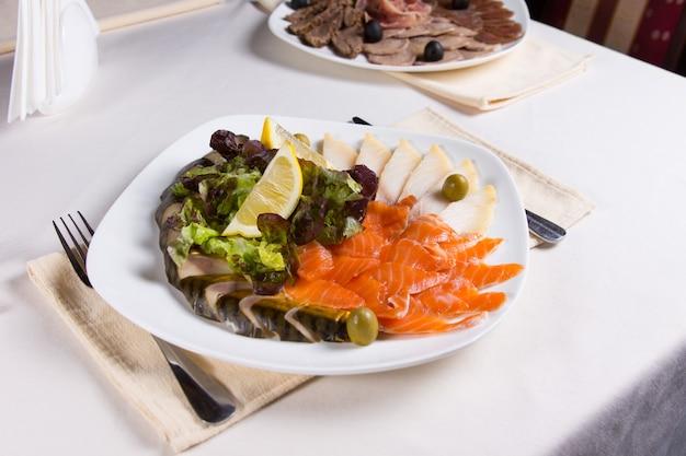 Gastronomische vers vleesschotel met groente- en citroenschijfjes op witte ronde plaat geserveerd op tafel.