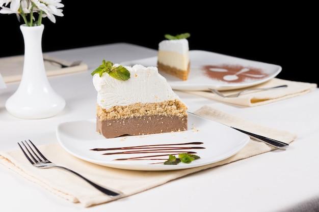 Gastronomische versgebakken cake plakjes op witte plaat, serveer op witte tafel met formele setting.