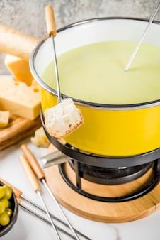 Gastronomische zwitserse fondue in traditionele fonduepot, met vorken, verschillende kazen, olijven, brood en druif