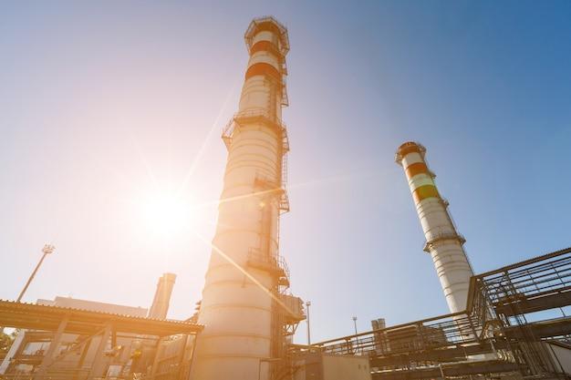 Gasturbineelektrische centrale op aardgas met schoorstenen van rode witte kleur tegen een blauwe hemel op een zonnige dag