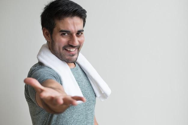 Gastvrije fitness man die op uitnodigende hand wijst; portret van een gelukkige, gezonde, zelfverzekerde, vriendelijke aziatische fitnessman die de hand wijst om je te verwelkomen en je vraagt om mee te doen; aziatische noord-indiase volwassen man model