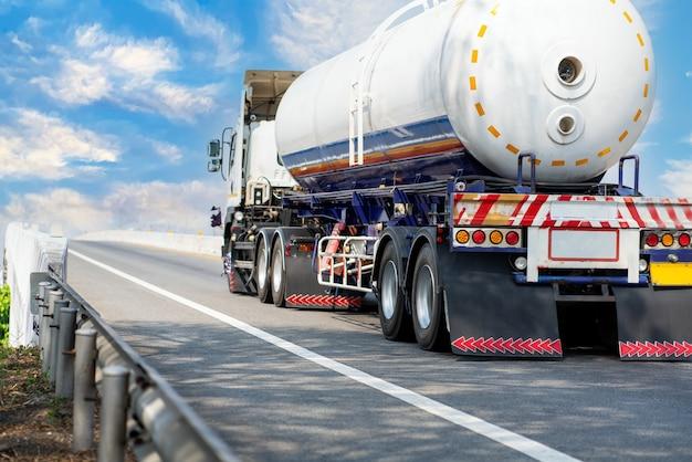 Gasvrachtwagen op snelwegweg met tankoliecontainer, transportconcept., import, export logistiek industrieel transport over land op de asfaltsnelweg met blauwe lucht