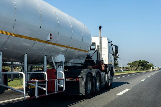 Gasvrachtwagen op wegweg met tankoliecontainer, vervoer op de asfaltuitgang met blauwe hemel