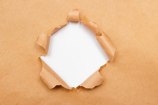 Gat in bruin knutselpapiervel met gescheurde randen.