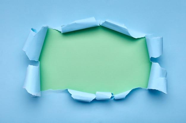 Gat in het blauwe papier. gescheurd. groen samenvatting