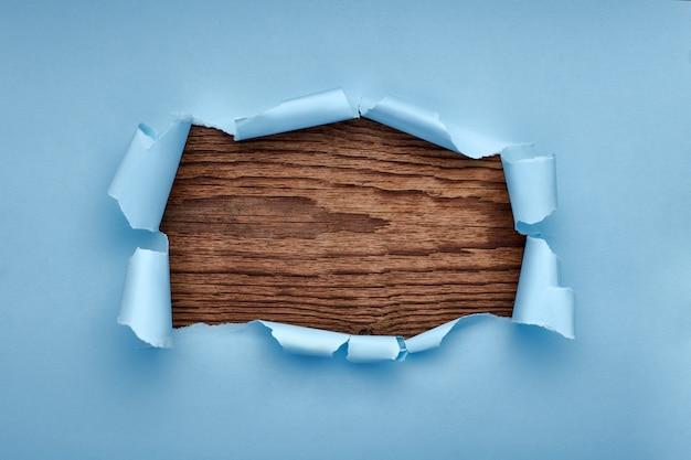 Gat in het blauwe papier. gescheurd. zwart houten. abstract