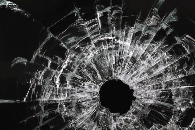 Gat in het glas van een kogel op een zwarte achtergrond