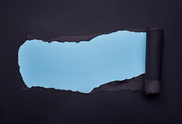 Gat in het zwarte papier. gescheurd. houten samenvatting