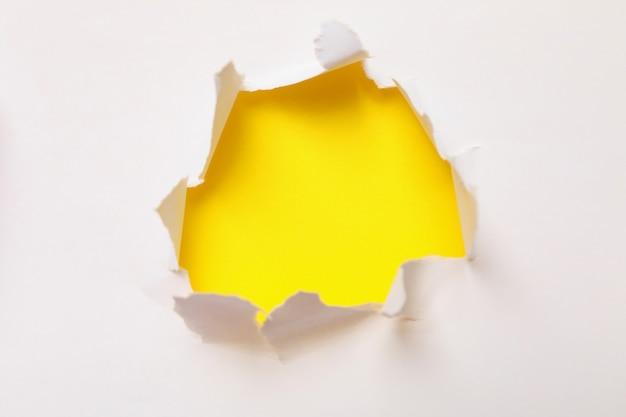 Gat in papier op gele achtergrond, ruimte voor tekst