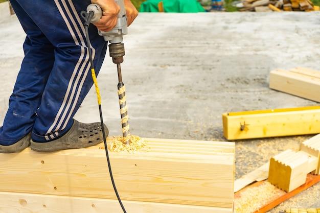 Gaten boren in gelamineerd fineerhout voor shkantov. bouw van het huis van de geprofileerde gelijmde staaf.