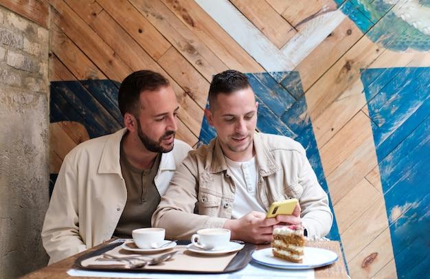 Gay mannelijk paar kijken naar een smartphone in een coffeeshop