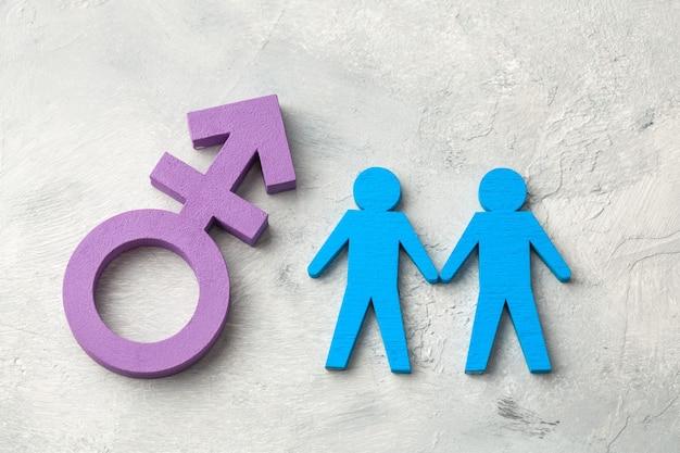 Gay paar hand in hand op transgender symbool achtergrond.
