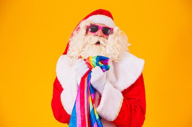 Gay santa claus met de lgbt-vlag. kerst gay pride concept. gay santa claus op gele achtergrond. sinterklaas is homo