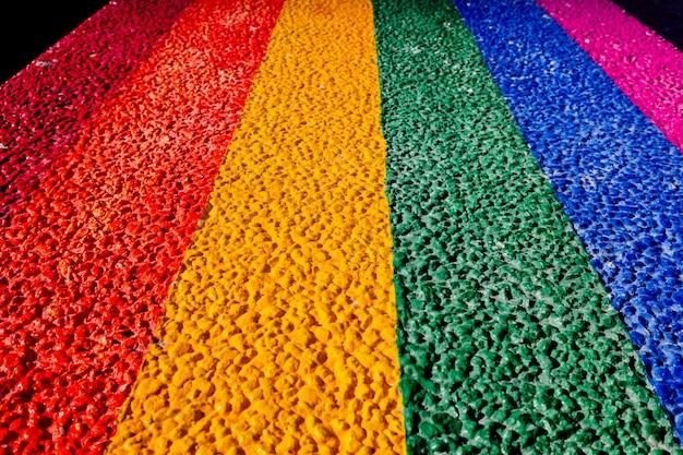 Gay vlag geschilderd op het harde cement van een stenen bankje.