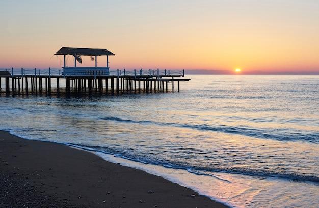 Gazebo op de houten pier in de zee met de zon bij zonsondergang.