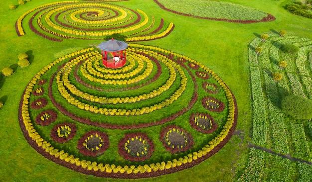Gazebo op het gazon naast een bloembed in het park. geweldige plek voor meditatie. luchtfoto.