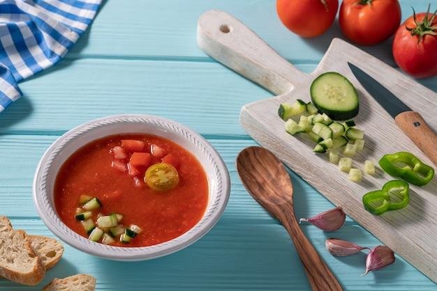 Gazpacho andaluz is een andalusische koude tomatensoep uit spanje met komkommer, knoflook, peper op lichtblauwe tafel