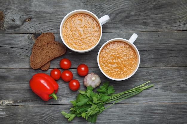 Gazpacho-soep en ingrediënten op donkere houten oppervlakte