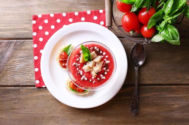 Gazpacho soep in glazen kom, op een houten achtergrond kleur