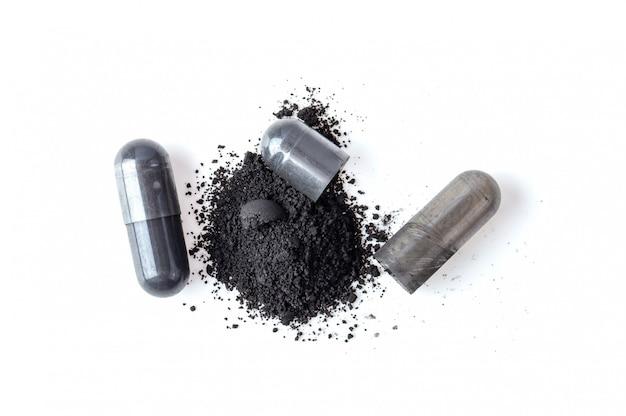 Geactiveerde houtskoolcapsule en poeder dat op wit wordt geïsoleerd. bovenaanzicht