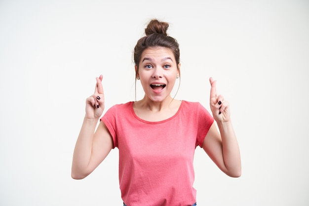 Geagiteerd jonge blauwogige bruinharige vrouw met casual kapsel vingers kruisen voor geluk en opgewonden kijken naar camera, geïsoleerd op witte achtergrond