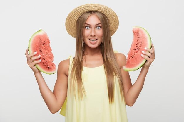 Geagiteerd jonge blauwogige mooie blonde vrouw met natuurlijke make-up vreugdevol kijken naar camera terwijl watermeloen, boater hoed en gele top dragen op witte achtergrond